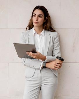 Widok z przodu elegancka kobieta trzymając tabletkę i filiżankę kawy