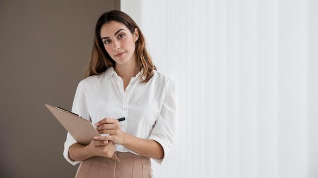 Widok z przodu eleganckiej bizneswoman gospodarstwa schowka