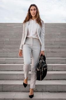 Widok z przodu eleganckiej bizneswoman na schodach na zewnątrz z torbą