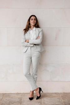 Widok z przodu eleganckiej bizneswoman pozuje na zewnątrz