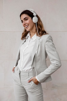 Widok z przodu eleganckiej bizneswoman, słuchanie muzyki na słuchawkach