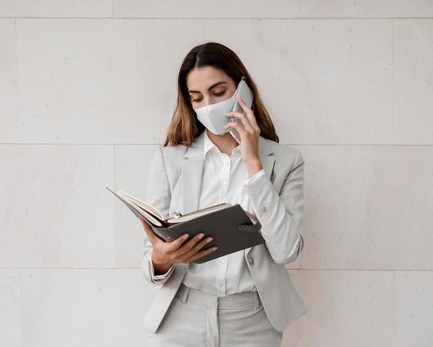 Widok z przodu eleganckiej bizneswoman z maską rozmawia przez telefon
