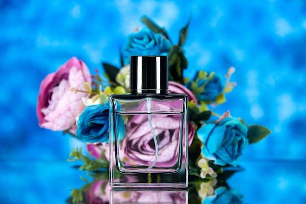 Widok z przodu eleganckiej butelki perfum i kolorowych kwiatów na brązowym tle