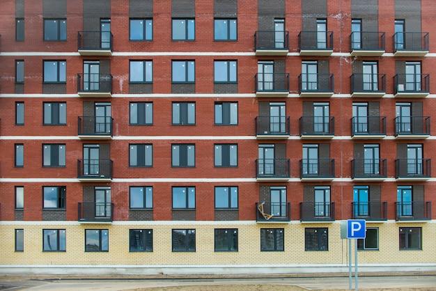 Widok z przodu elewacji nowego nowoczesnego budynku. pełnoklatkowa konstrukcja przeznaczona na reklamy i witryny.