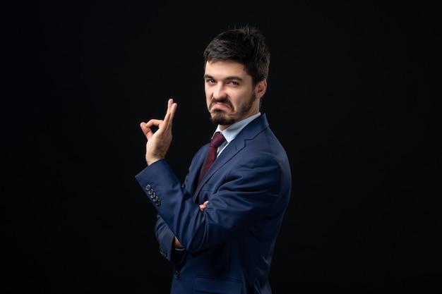 Widok z przodu emocjonalnego brodatego mężczyzny wykonującego doskonały gest na izolowanej ciemnej ścianie