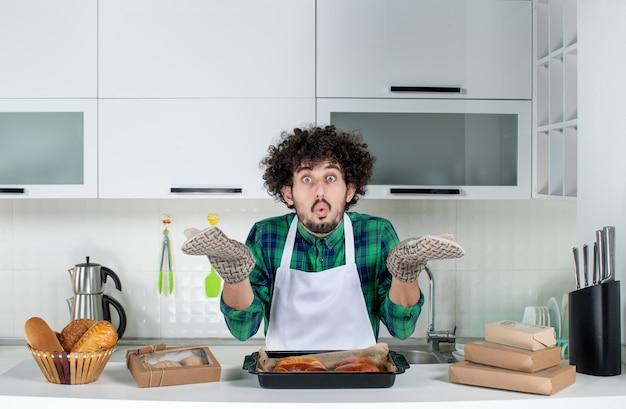 Widok z przodu emocjonalnego faceta noszącego uchwyt stojący za stołem ze świeżo upieczonym ciastem na nim w białej kuchni