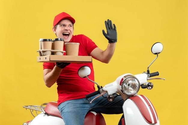 Widok z przodu emocjonalnego kuriera człowieka w czerwonej bluzce i rękawiczkach w masce medycznej dostarczania zamówienia siedzącego na skuterze przechowującym zamówienia