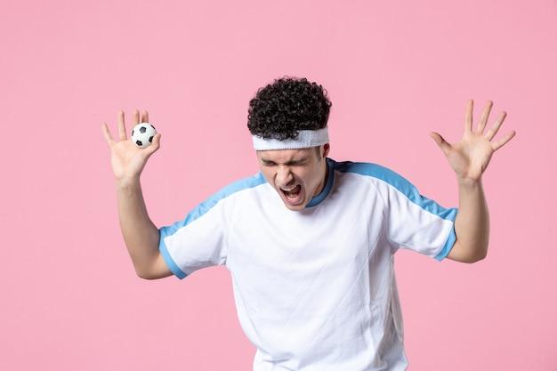 Widok z przodu emocjonalny piłkarz w strojach sportowych z małą piłką