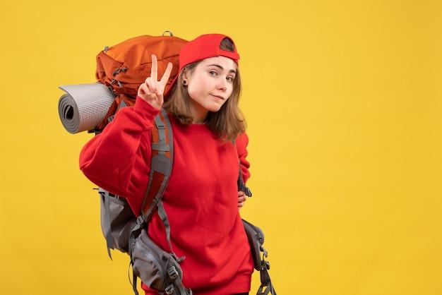 Widok z przodu fajna podróżniczka z plecakiem, wskazująca znak zwycięstwa