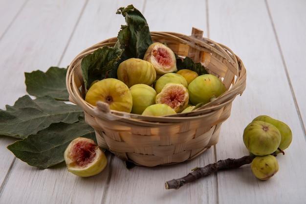 Widok z przodu figi w koszu z gałęzi i liści na białym tle