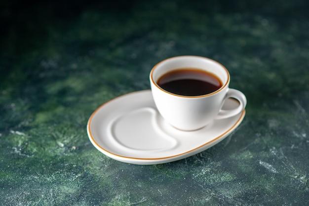 Widok z przodu filiżanka herbaty w białej płytce na ciemnej powierzchni ceremonia kolorów śniadanie rano zdjęcie chleb szklany napój