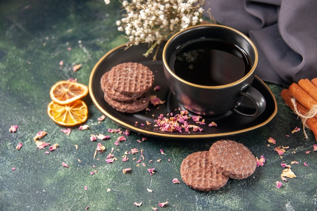 Widok z przodu filiżanka herbaty w czarnej filiżance i talerz z herbatnikami na ciemnoniebieskiej powierzchni koloru szkła cukrowego śniadanie deser ciasto ceremonia cookie