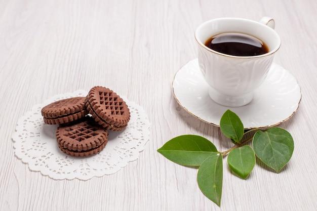 Widok z przodu filiżanka herbaty z ciasteczkami na białym stołowym ciastku z cukrem słodkim herbatnikiem