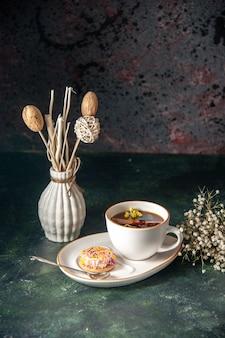 Widok z przodu filiżanka herbaty z małym słodkim ciastkiem na talerzu na ciemnej ścianie ceremonia szklana słodki tort śniadaniowy zdjęcie rano deser kolory