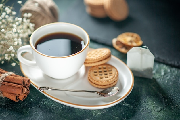 Widok z przodu filiżanka herbaty ze słodkimi ciasteczkami na ciemnej powierzchni chleb ceremonia picia śniadanie rano zdjęcie ciasto cukrowe słodkie kolory szkła