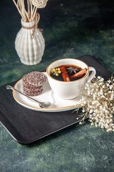 Widok z przodu filiżanka herbaty ze słodkimi ciasteczkami na talerzu i tacy na ciemnej powierzchni ceremonia szklana słodki kolor ciasta deser śniadaniowy