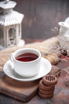Widok z przodu filiżankę herbaty z ciasteczkami na ciemnym stole ciemny herbatnik