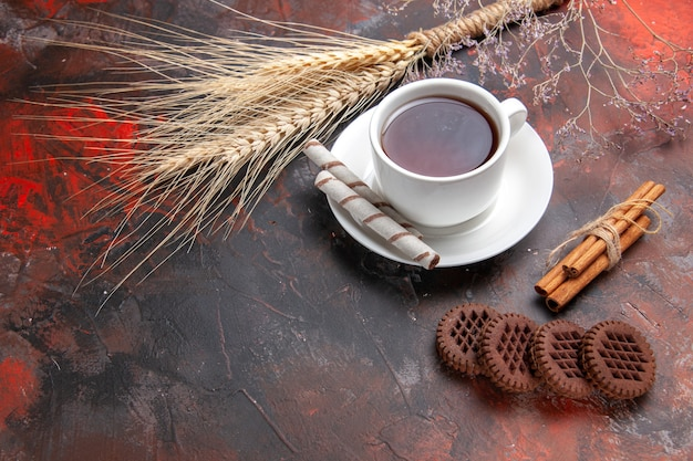 Widok z przodu filiżankę herbaty z ciasteczkami na ciemnym stole herbata ciemna