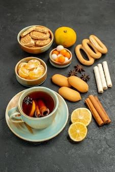 Widok z przodu filiżankę herbaty z cukierkami, herbatnikami i owocami na szarym stole herbata słodkie ciasteczko