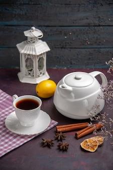 Widok z przodu filiżankę herbaty z cynamonem i czajnikiem na ciemnej powierzchni napój herbaciany w kolorze cytryny