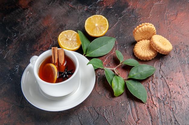 Widok z przodu filiżankę herbaty z cytryną i ciasteczkami na ciemnym tle