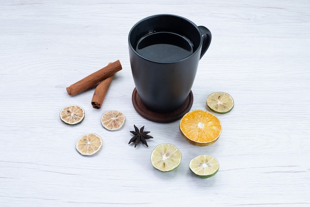 Widok z przodu filiżankę herbaty z cytryną i cynamonem na lekkim biurku