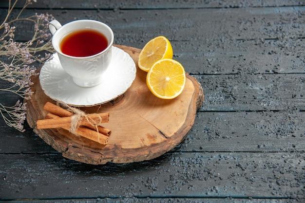 Widok z przodu filiżankę herbaty z cytryną na ciemnym tle