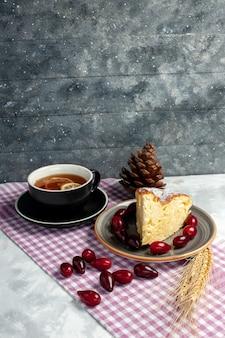 Widok z przodu filiżankę herbaty z kawałkiem pysznego ciasta na jasnobiałej powierzchni