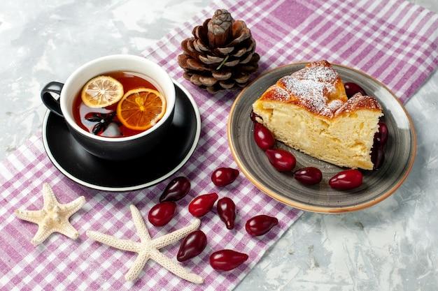 Widok z przodu filiżankę herbaty z pysznym kawałkiem ciasta na białej powierzchni