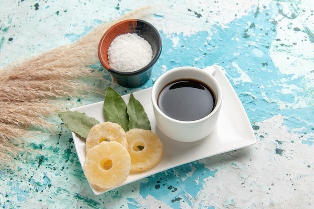 Widok z przodu filiżanki herbaty z suszonymi krążkami ananasa na jasnoniebieskiej powierzchni