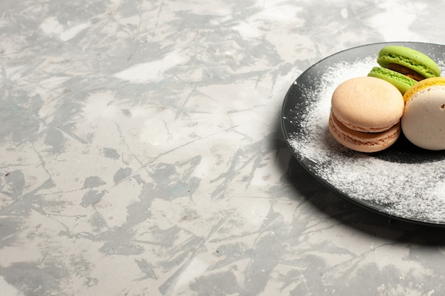 Widok z przodu francuskie macarons pyszne kolorowe ciasta wewnątrz płyty na białej powierzchni