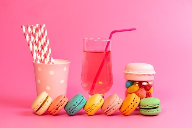 Widok z przodu francuskie macarons ze świeżym napojem, kolorowymi cukierkami i cukierkami w sztyfcie na różowych, ciastkowych cukierniach