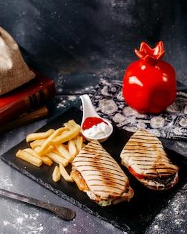 Widok z przodu frytki z pokrojoną kanapką wewnątrz czarnego talerza na szarym biurku