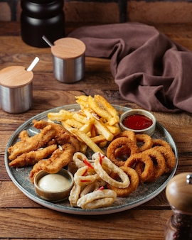 Widok z przodu frytki ze smażonymi skrzydełkami kurczaka i krążkami cebuli z keczupem na brązowym drewnianym biurku jedzenie posiłek ziemniaczany