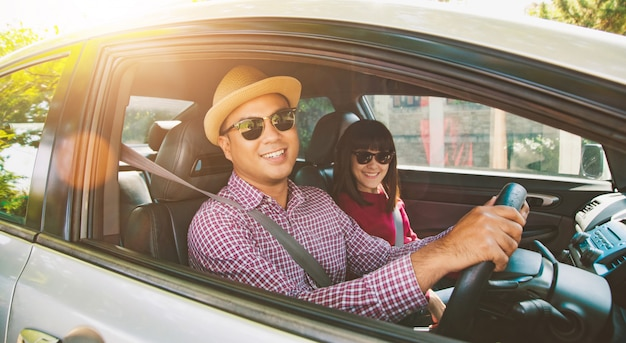 Widok z przodu funny moment para azjatyckich mężczyzna i kobieta siedzi w samochodzie. koncepcja podróży.