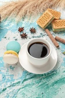 Widok z przodu gofry i makaroniki z filiżanką herbaty na niebieskiej powierzchni ciasto biszkoptowe i cukrowe słodkie ciasteczko