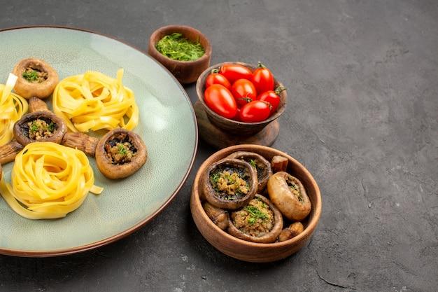 Widok z przodu gotowane grzyby z makaronem ciasta na ciemnym stole danie obiadowy posiłek