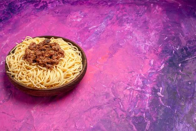 Widok z przodu gotowane spaghetti z mielonym mięsem na jasnoróżowym naczyniu stołowym w kolorze ciasta makaronowego