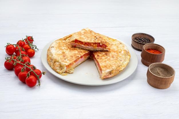 Widok z przodu gotowanego ciasta warzywnego wewnątrz białej płytki ze świeżymi czerwonymi pomidorami na białej powierzchni