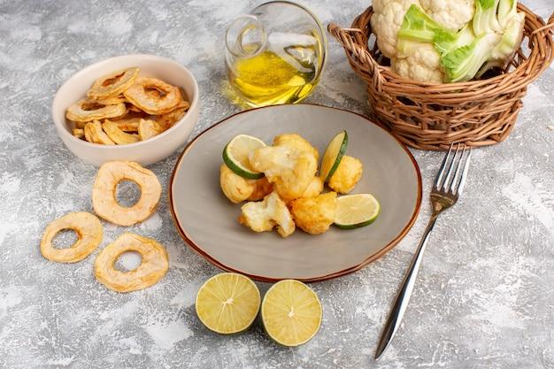 Widok z przodu gotowanego kalafiora w plasterkach wewnątrz talerza z cytryną i olejem na jasnej białej ścianie
