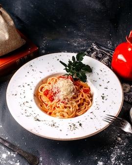 Widok z przodu gotowanego makaronu wraz ze świeżym zielonym liściem i czerwonymi pomidorami wewnątrz białego talerza na szarym biurku