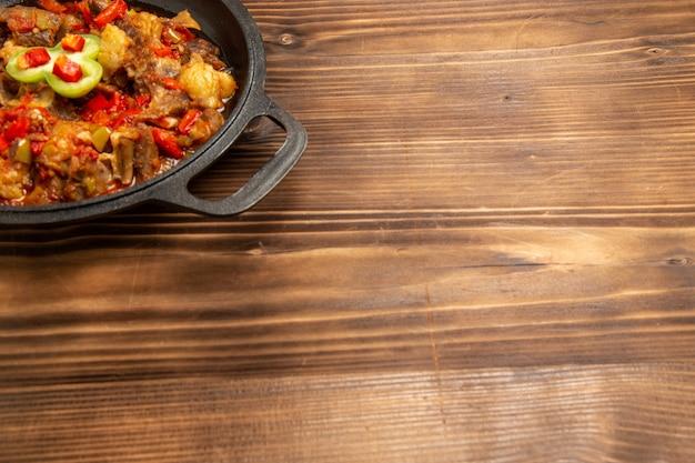 Widok z przodu gotowanego posiłku warzywnego na patelni na brązowej powierzchni