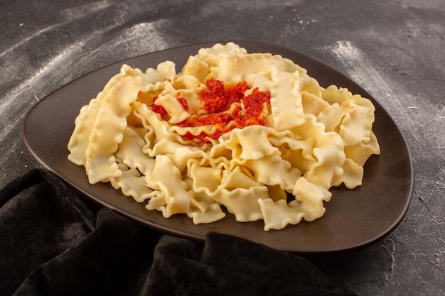 Widok z przodu gotowanego włoskiego makaronu z sosem pomidorowym wewnątrz płyty na szarej powierzchni
