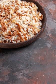 Widok z przodu gotowany ryż z plastrami ciasta na ciemnej powierzchni zdjęcie danie posiłek ciemne jedzenie