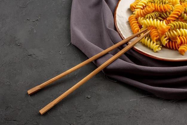 Widok z przodu gotowany włoski makaron niezwykły spiralny makaron wewnątrz talerza na ciemnej przestrzeni
