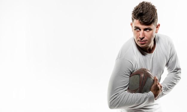 Widok z przodu gracza rugby płci męskiej, pozowanie z piłką i miejsce na kopię