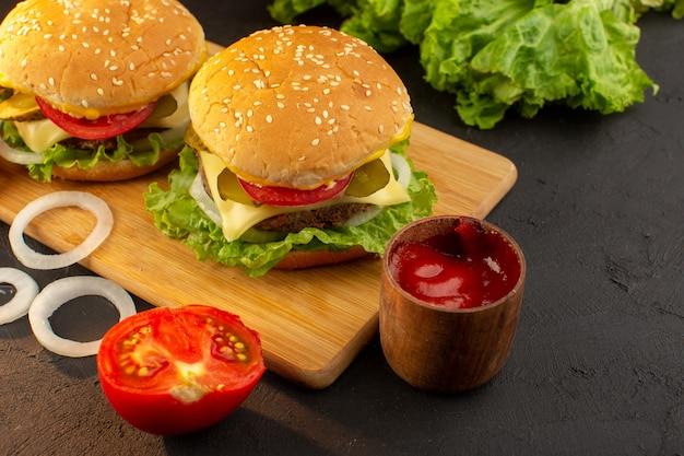 Widok z przodu hamburgery z kurczaka z serem i zieloną sałatą na drewnianym biurku i kanapkowy posiłek typu fast-food