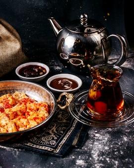 Widok z przodu herbaty wraz ze smażonymi jajkami i czerwonymi pomidorami na szarym biurku