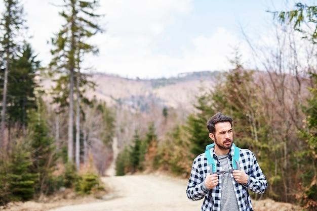 Widok z przodu idącego mężczyzny z plecakiem podziwiającego widok
