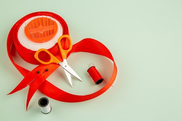 Widok z przodu igły i kokarda w kolorze czerwonym na jasnozielonej powierzchni szpilka zdjęcie szyć kolorowe szycie odzieży szycie igłą